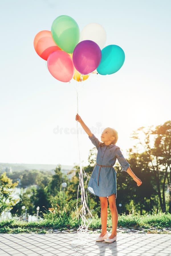 Dziewczyna trzyma kolorowych balony rozciąga dreamin i niebo zdjęcia stock