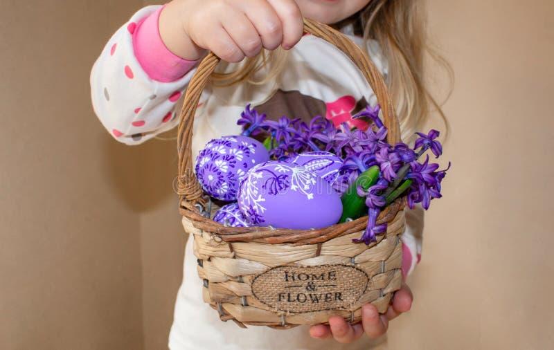Dziewczyna trzyma kosz z malującymi kwiatami w lilych kwiatach dla wielkanocy i jajkami, zdjęcia stock