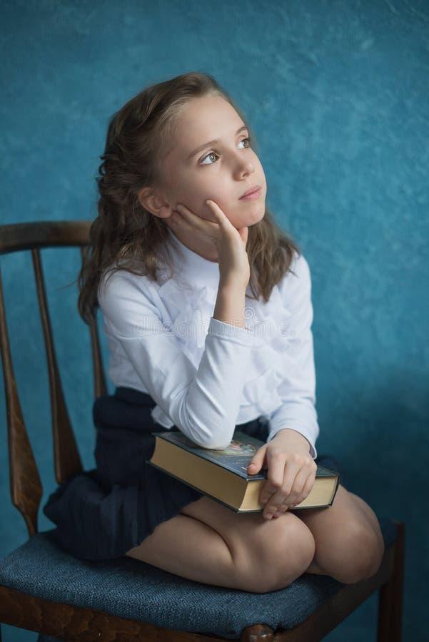 Dziewczyna trzyma książkę na jej główkowaniu i podołku zdjęcie royalty free