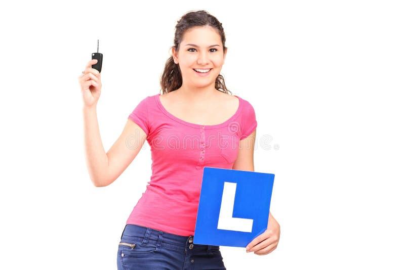 Dziewczyna trzyma l znak i samochodowy klucz obrazy stock