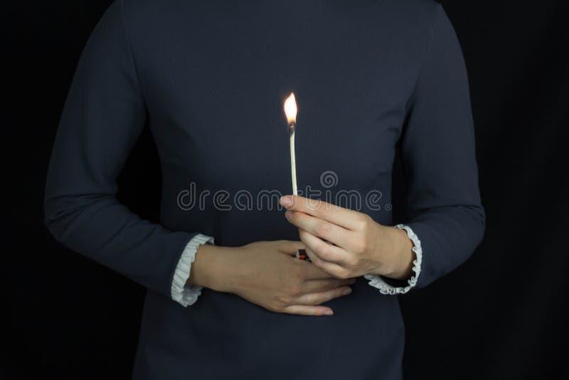 Dziewczyna trzyma płonącego dopasowanie przeciw tłu żołądek, pali w żołądku, zgaga, czarny tło obraz stock