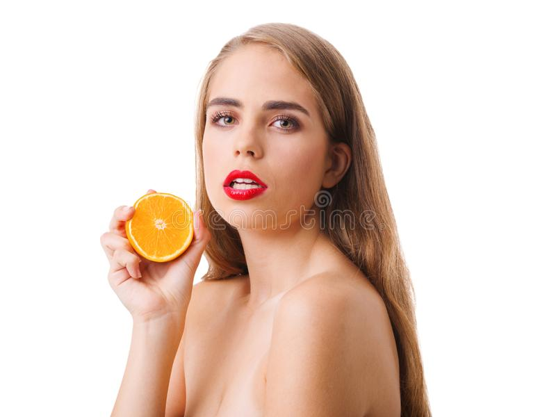 Dziewczyna trzyma połówkę pomarańcze w jej ręce na białym odosobnionym tle obrazy royalty free