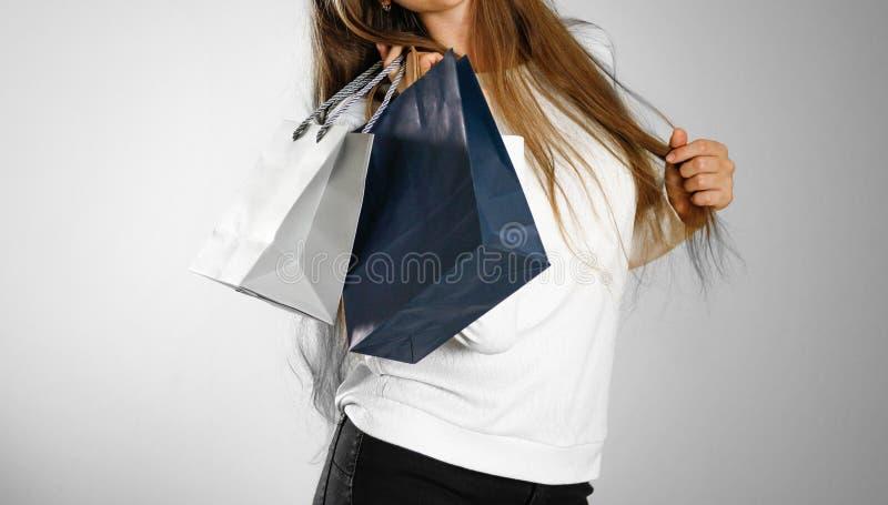 Dziewczyna trzyma popielate prezent torby i błękit z bliska Backg fotografia stock