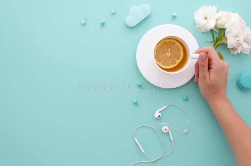 Dziewczyna trzyma ranek herbaciany z cytryną w jej rękach na nowym tiffany tle z białych róż biurem i słuchawkami obrazy royalty free