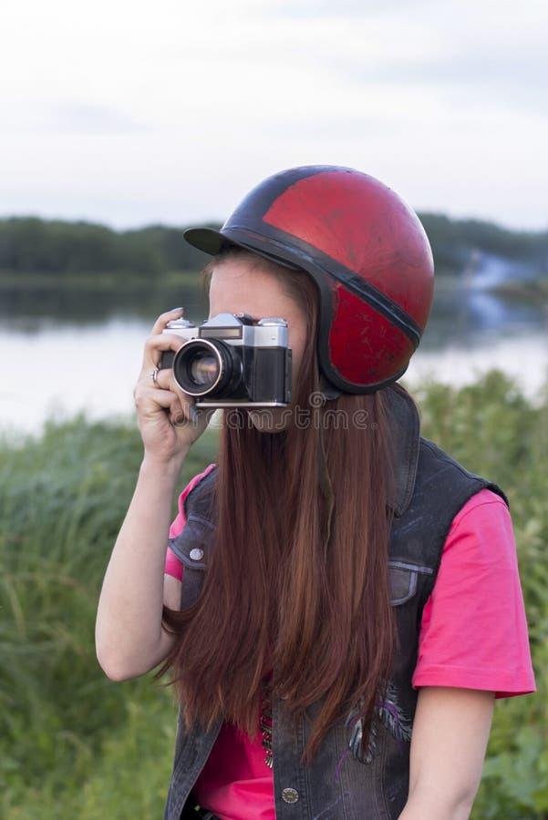 Dziewczyna trzyma rocznik kamerę w retro hełmie obrazy royalty free