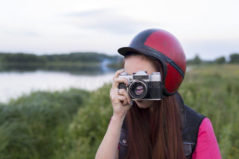 Dziewczyna trzyma rocznik kamerę w retro hełmie zdjęcia stock