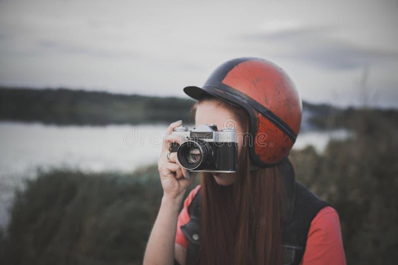 Dziewczyna trzyma rocznik kamerę w retro hełmie obraz royalty free