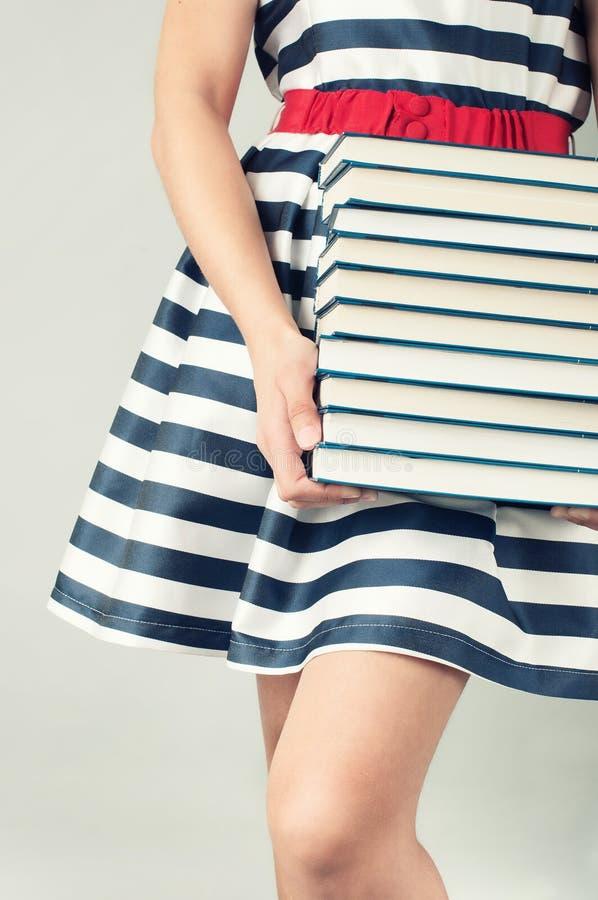 Dziewczyna trzyma stertę książki w pasiastej sukni obraz royalty free