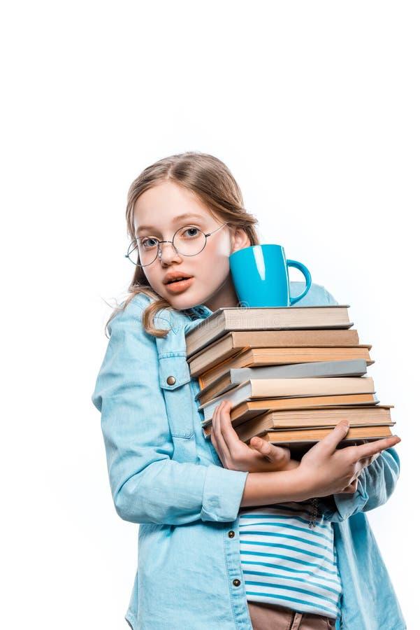 Dziewczyna trzyma stertę książki z filiżanką na odgórnej i patrzeje kamerze w eyeglasses fotografia stock