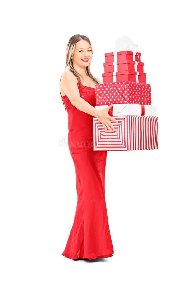 Dziewczyna trzyma stos teraźniejszość w czerwieni sukni fotografia royalty free