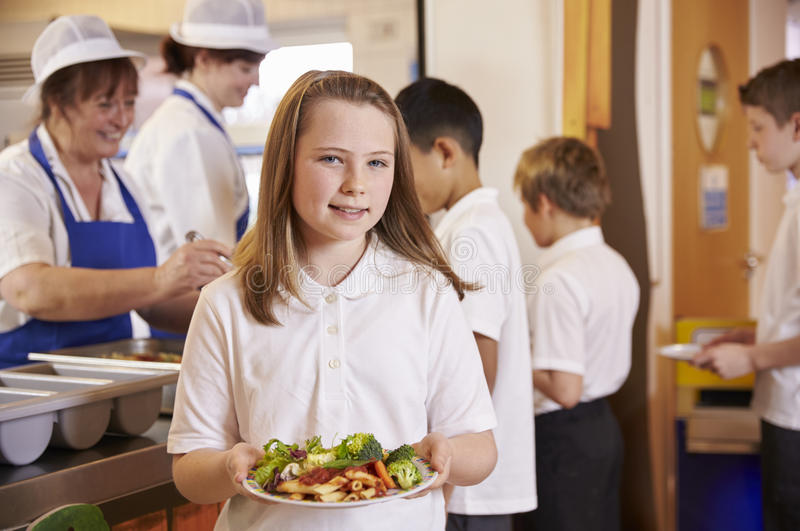 Dziewczyna trzyma talerza jedzenie w szkolnym bufecie, przewodzi obraca obrazy royalty free