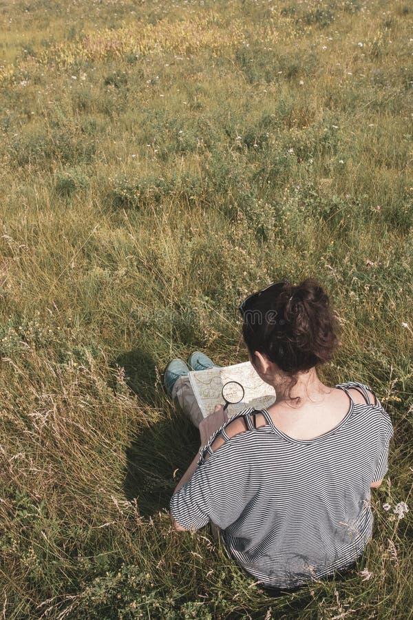 Dziewczyna turystka w pasiastym swetrze siedzi na polu wÅ›ród trawy i patrzy na mapÄ™ przez powiÄ™kszenie zdjęcia stock