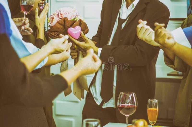 Dziewczyna uśmiechająca się z podnieceniem Wśród grupy przyjaciele przy przyjęciem, gdy biznesmen dać kwiaty i sercowatego symbol zdjęcia stock