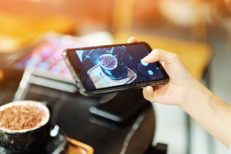 Dziewczyna używał jej smartphone dla bierze obrazek na kawowej kawiarni zdjęcie stock