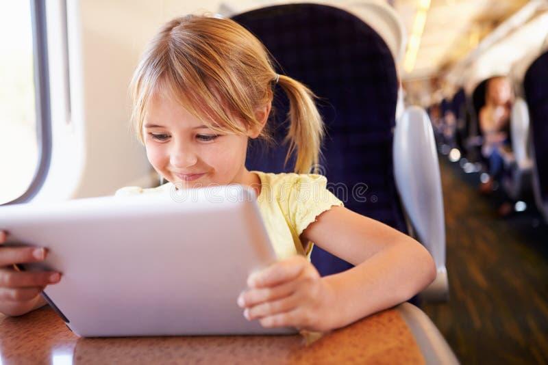 Dziewczyna Używa Cyfrowej pastylkę Na pociągu obrazy stock