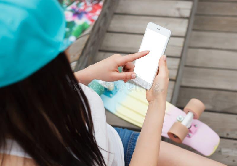 Dziewczyna używa dużego nowożytnego phablet smartphone z pustym ekranem zdjęcie royalty free