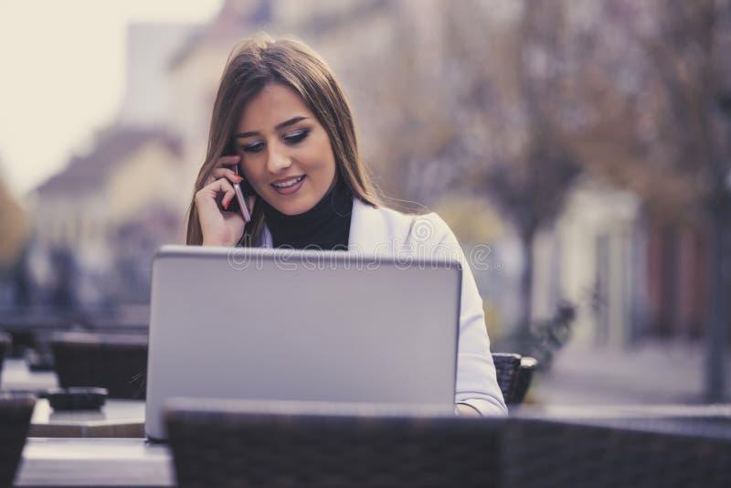Dziewczyna używa laptop na kreskowej i dzwoni obsłudze klienta na mobi zdjęcie stock