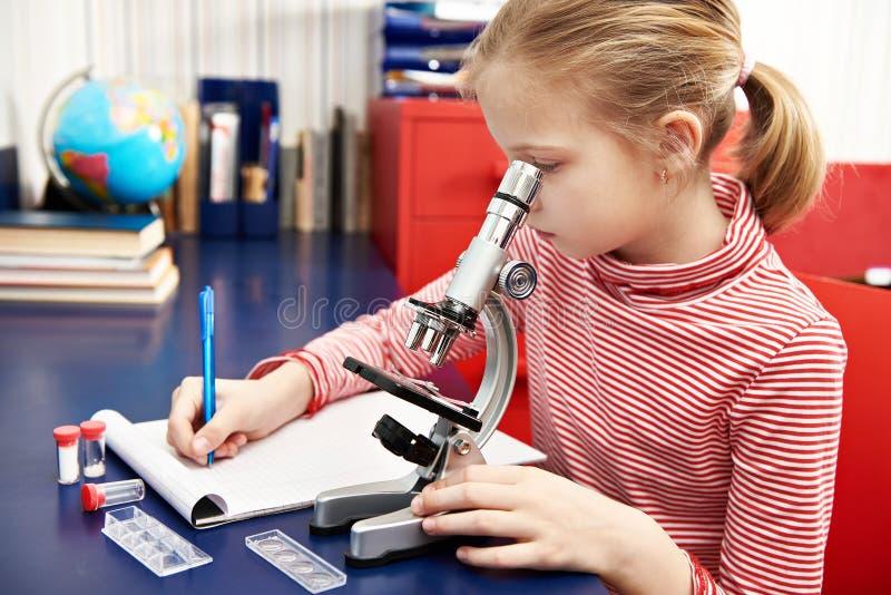 Dziewczyna używa mikroskop i pisze rezultatach zdjęcie stock