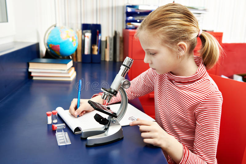 Dziewczyna używa mikroskop i pisze rezultatach obrazy royalty free