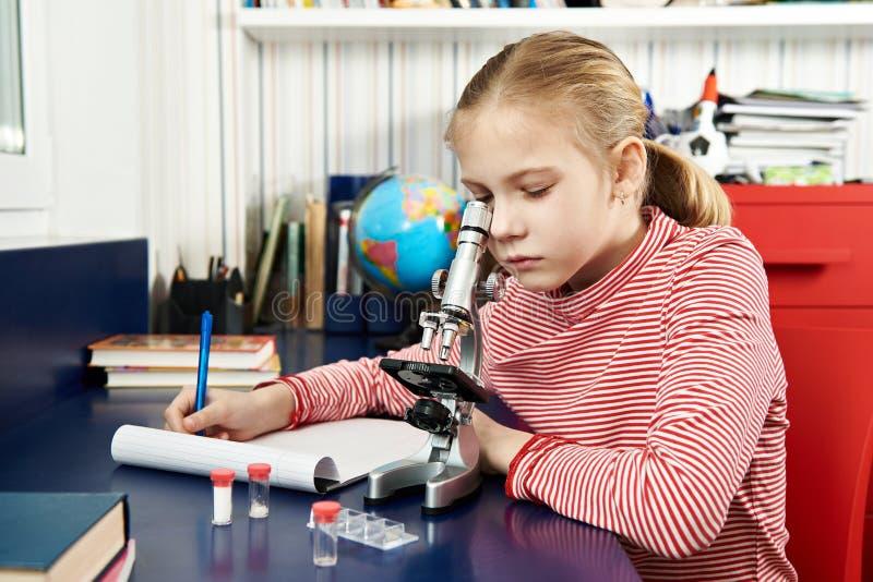 Dziewczyna używa mikroskop i pisze rezultatach fotografia stock