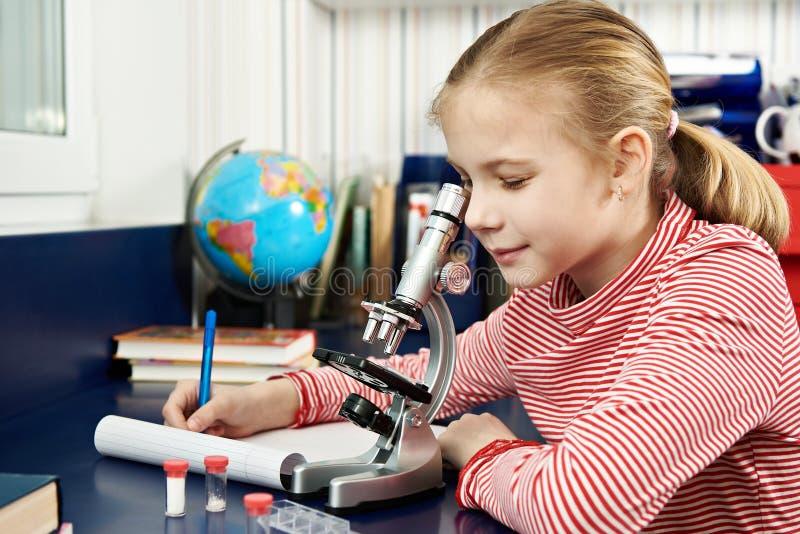 Dziewczyna używa mikroskop i pisze rezultatach obraz stock