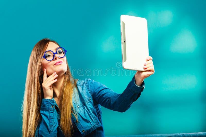 Dziewczyna używa pastylkę bierze obrazkowi ona błękitnego kolor obrazy stock
