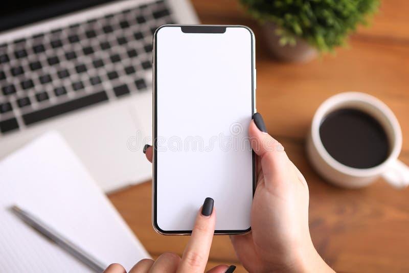 Dziewczyna używa smartphone przy pracą Biel ekran fotografia royalty free