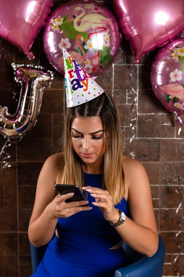 Dziewczyna używa smartphone przy przyjęciem urodzinowym fotografia royalty free