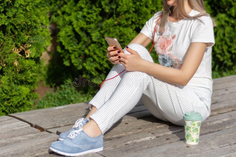Dziewczyna u?ywa smartphone Kobiety obsiadanie na ławce obok filiżanka kawy w parku na pogodnym wiosna dniu obraz stock