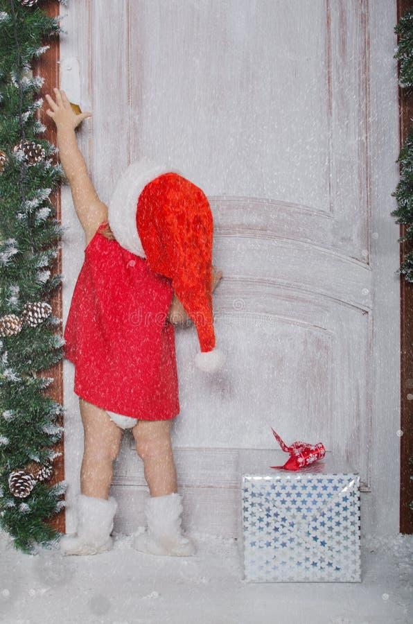 Dziewczyna ubierająca jako Santa otwiera drzwi pod śniegiem obrazy royalty free