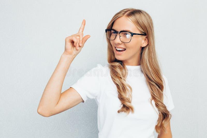 Dziewczyna uczeń w szkłach, w białej koszulce, siedzący na podłoga, mieć pomysł i patrzejący kamerę na popielatym ściennym tle, obrazy stock