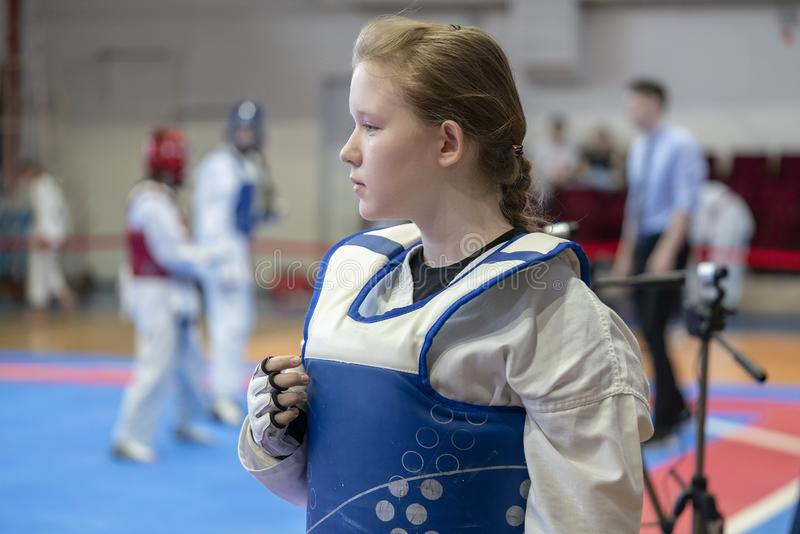 Dziewczyna uczestniczy w Taekwondo rywalizacjach w b??kitnej ochronnej kamizelce na tle Taekwondo rywalizacje obraz stock