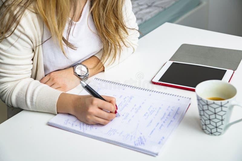 Dziewczyna uczy się i pisze w notebooku z piórem obraz royalty free