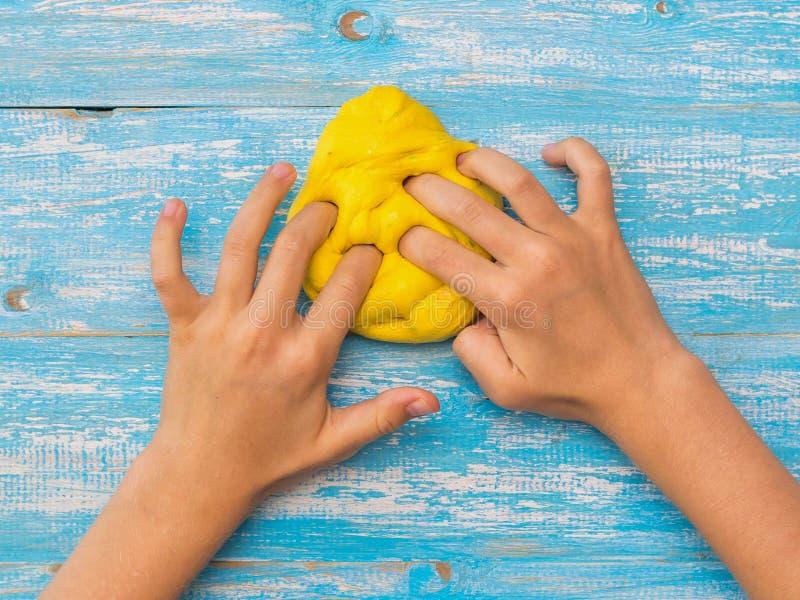 Dziewczyna ugniata kolor żółtego szlamowego na błękitnym drewnianym stole fotografia royalty free