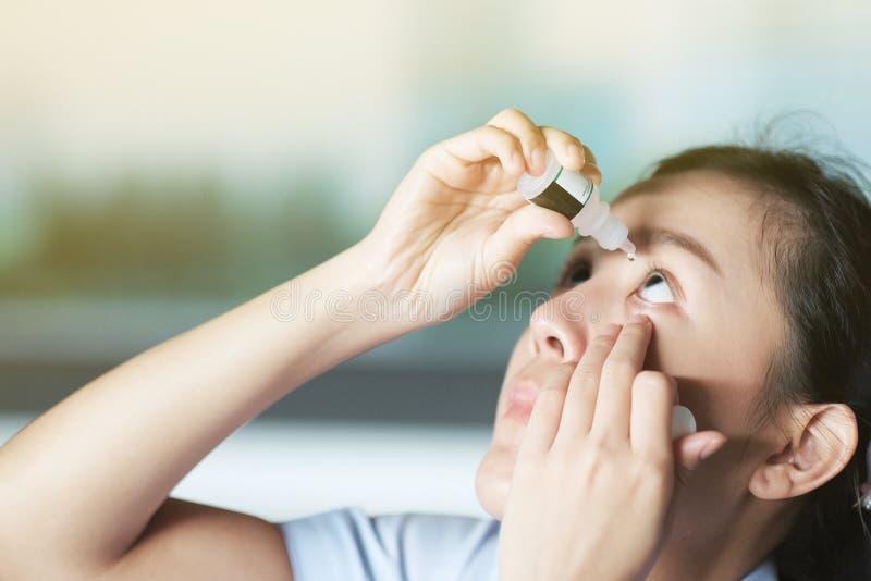 Dziewczyna upuści sztuczne łzy, aby zmniejszyć podrażnienie oka fotografia stock