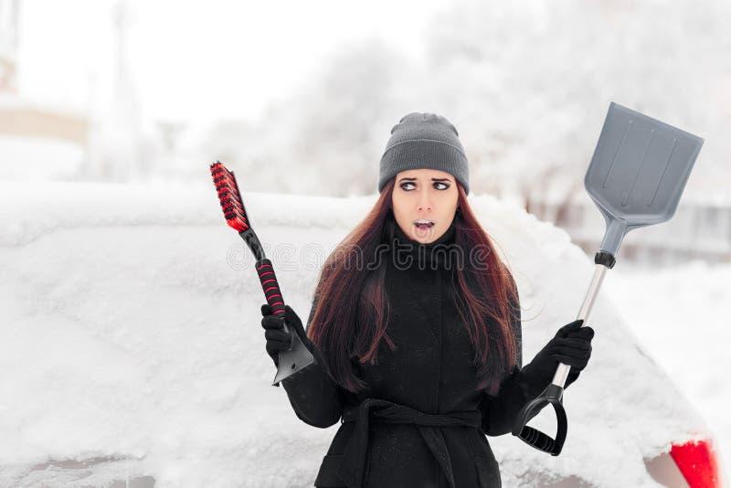 Dziewczyna Usuwa śnieg od samochodu z muśnięciem i łopatą zdjęcia royalty free