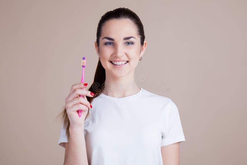 Dziewczyna utrzymuje toothbrush i ono uśmiecha się zdjęcia royalty free