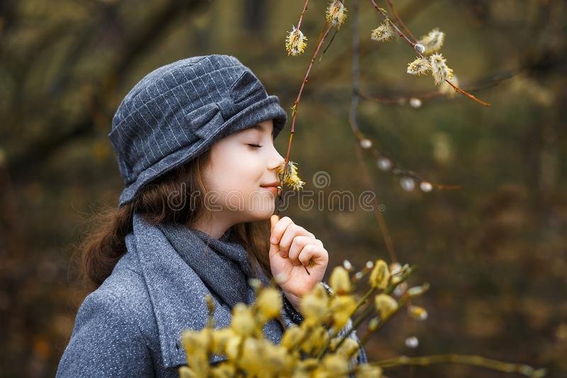 Dziewczyna wącha gałązki w popielatym żakiecie i ślicznym szarym kapeluszu z wierzbową gałąź gałązki w lesie w wczesnej wiośnie zdjęcia stock