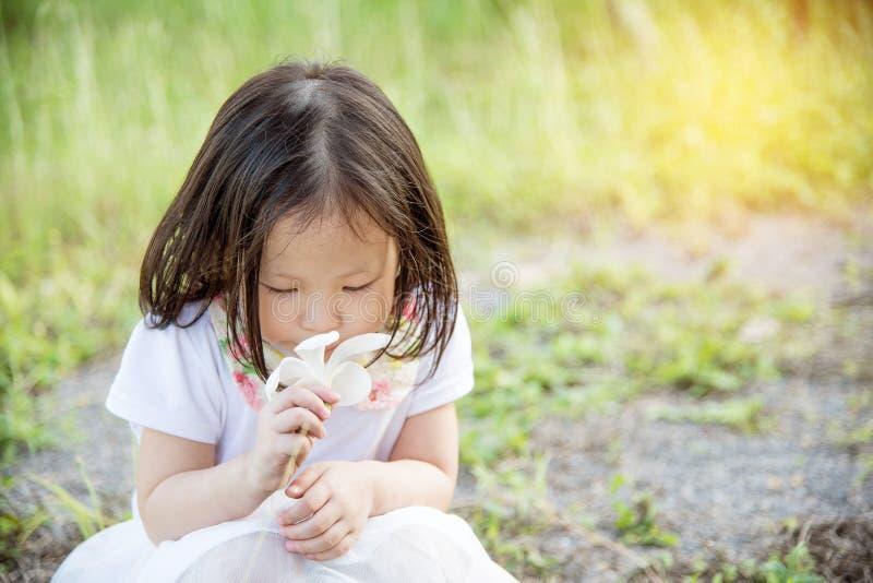 Dziewczyna wącha kwiatu w parku zdjęcia stock