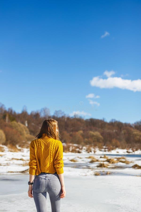 Dziewczyna w żółtym pulowerze z krótkim ostrzyżeniem stoi z powrotem na lodzie rzeka zdjęcie royalty free