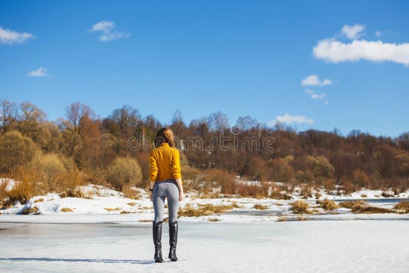Dziewczyna w żółtym pulowerze z krótkim ostrzyżeniem stoi z powrotem na lodzie rzeka obrazy stock