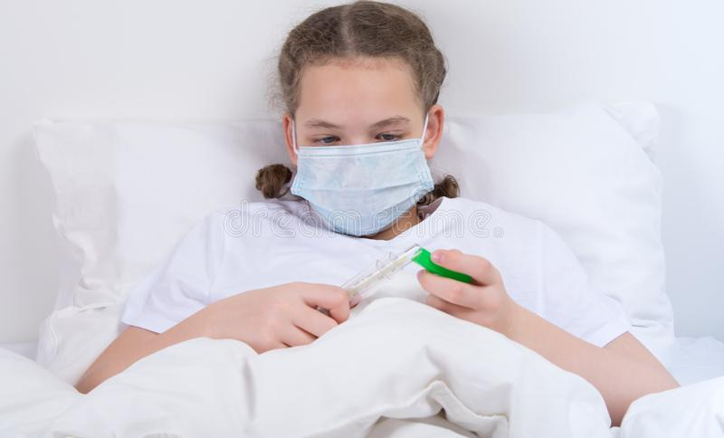 dziewczyna w łóżku, w medycznej masce sprawdza temperaturę ciało, trzyma termometr zdjęcia royalty free