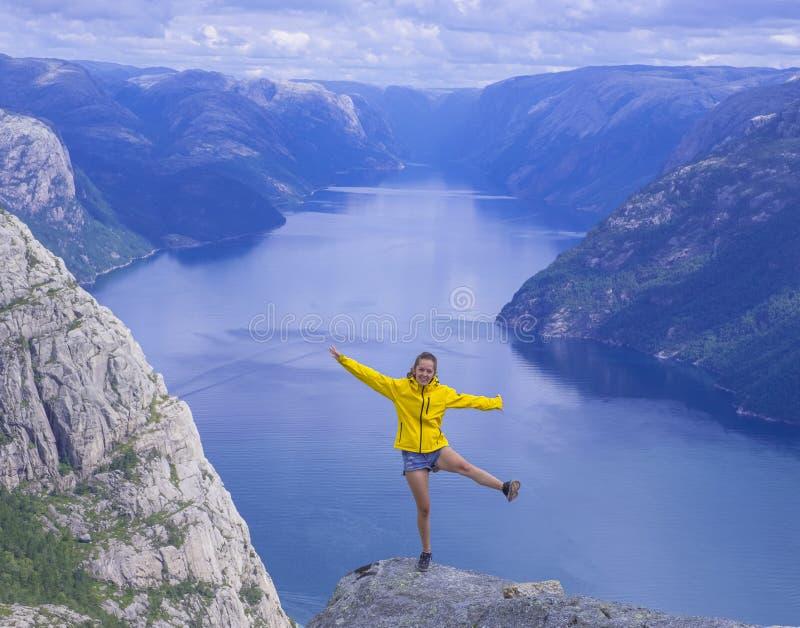 Dziewczyna w żółtej kurtce z rękami podnosił patrzeć Lysefjord fjord od Preikestolen obraz royalty free