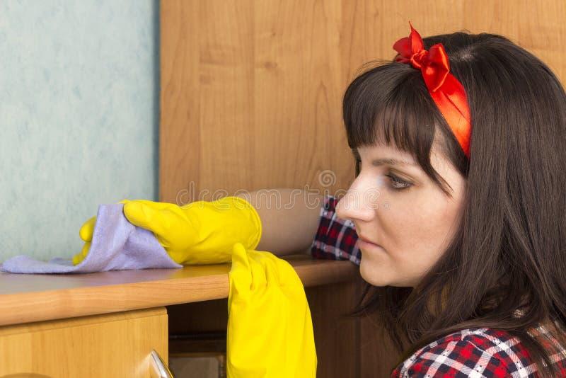 Dziewczyna w żółtych rękawiczek wytarciach odkurza, zakończeń potomstwa obrazy royalty free