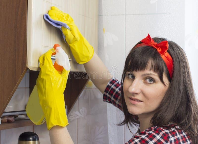 Dziewczyna w żółtych rękawiczkach myje szafkę w kuchni, zakończenia urządzenie obraz stock