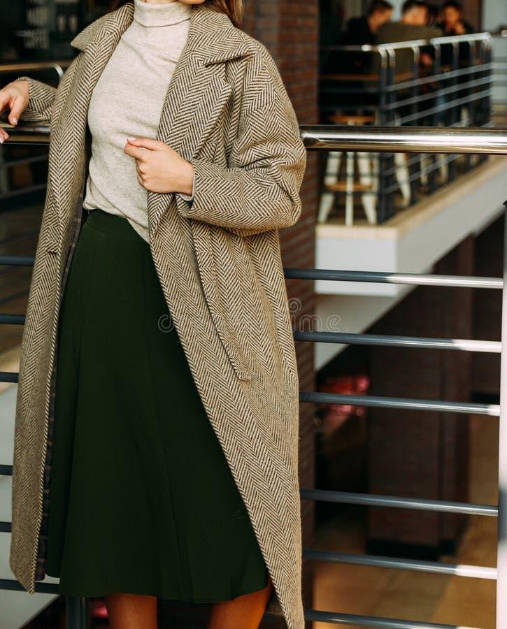 Dziewczyna w żakiecie beżowym pulowerze i, zieleń, długa spódnica, stojaki blisko poręcza, opiera na metalu poręczu odpoczynek, p obrazy stock