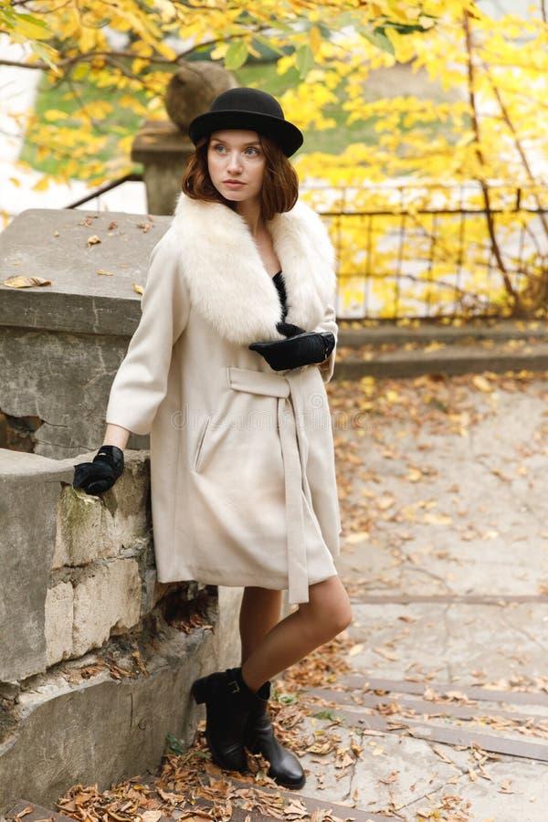 Dziewczyna w żakiecie i czarnym kapeluszu stoi w jesień parku przyglądającym up i retro _ obrazy stock