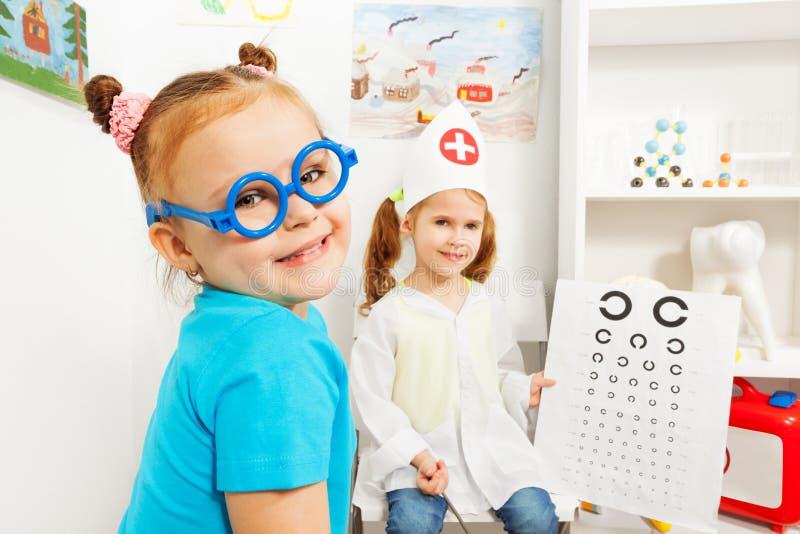 Dziewczyna w błękit zabawki szkłach przy oftalmologa pokojem fotografia stock