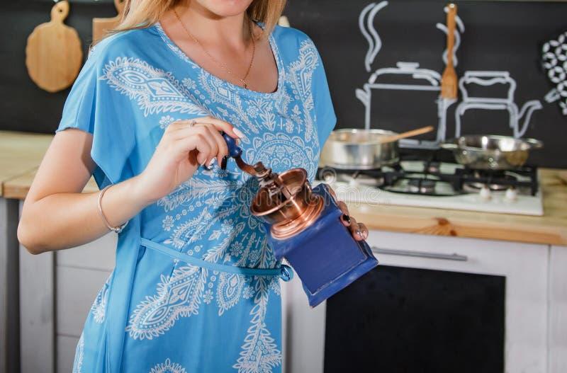 Dziewczyna w błękitnej sukni mleje kawę Dziewczyna z kawowym ostrzarzem obraz royalty free