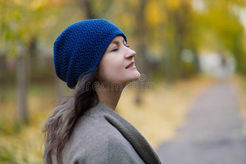 Dziewczyna w błękitnym kapeluszu na tle i żakiecie jesień liście klonowi i drzewa obraz royalty free